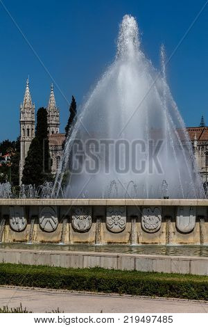 Empire Square fountain with the Jeronimos Monastery in the background in Lisbon Portugal. The square commemorates the Portuguese Empire and was built for the Portuguese World Exhibition in 1940.