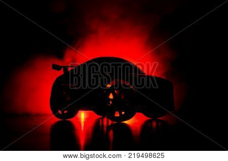 The Car In The Shadows With Glowing Lights In Low Light, Or Silhouette Of Sport Car Dark Background.