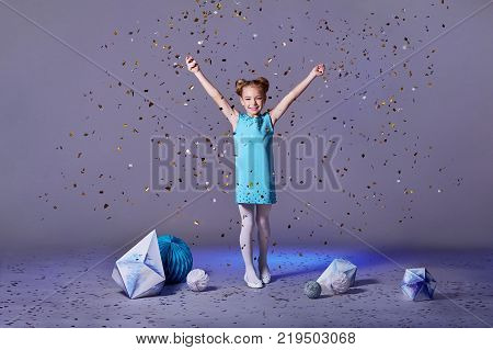 Cute baby girl dresses pretty model enjoying holiday and throwing confetti.happy holidays images.kids party dresses.Cheerful girl in an elegant turquoise dress with a hair, make-up.