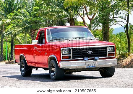 Palenque Mexico - May 22 2017: Red pickup truck Ford F-150 in the town street.