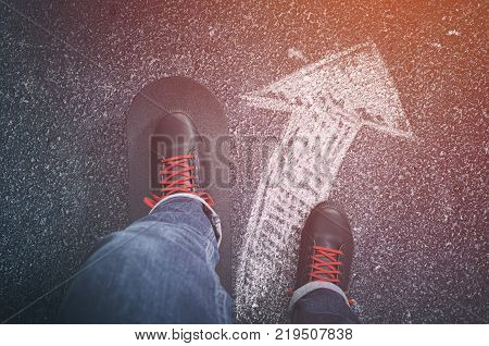 Going The Right Way. Sneakers with skateboard and arrow on asphalt road.