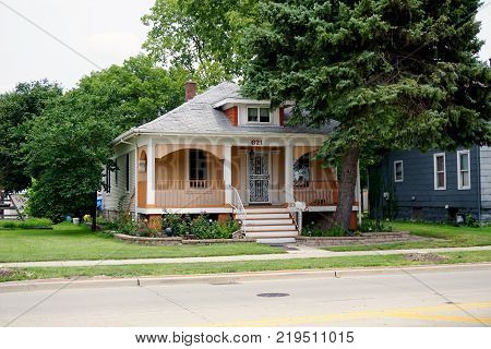 JOLIET, ILLINOIS / UNITED STATES - JULY 26, 2017: A small, single family, Cape Code style home, with a front porch, on Plainfield Road in Joliet.