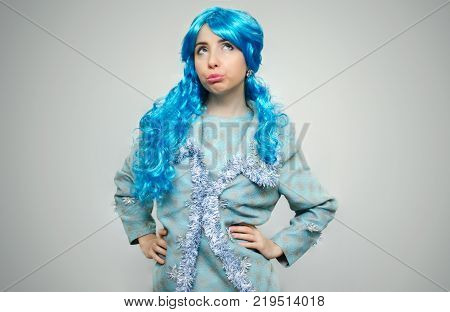 Dissatisfied offended and recentful girl pout her mouth with blue hair isolated on gray background.