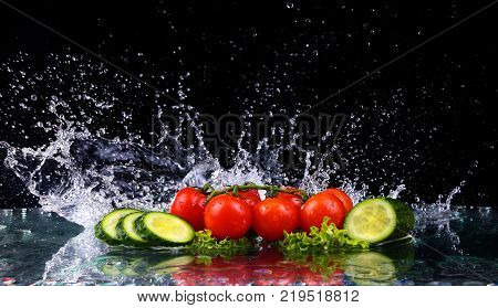 Studio shot with freeze motion of cherry tomatoes and slices of cucumber in water splash on black background, with copy space