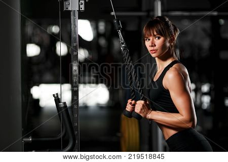 The girl in the gym trains the hands in the simulator