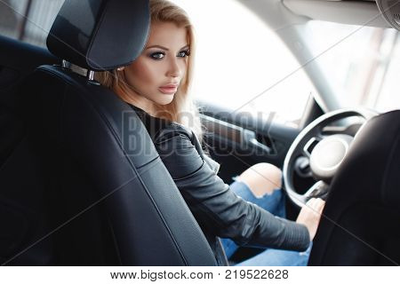 Young woman driving a car in the city.Successful, attractive, beautiful, young woman - blonde, sitting at the wheel of an expensive car. Portrait of a beautiful woman in a car looking out of the window and smiling. Travel and vacations concepts