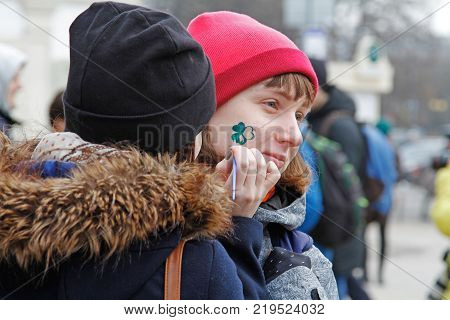 Moscow Russia - March 18 2017: Artist draws a Shamrock on girl's face at the St. Patrick's Day Parade in the park Sokolniki in Moscow