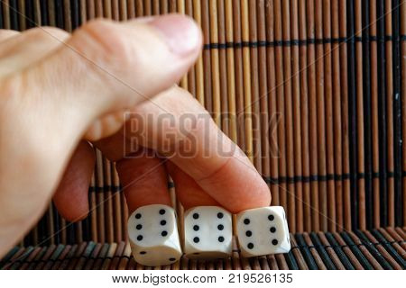 Stack Of Three White Plastic Dices In Man's Hand On Brown Wooden Table Background. Six Sides Cube Wi