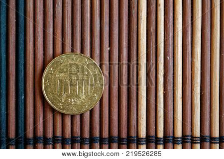 One Euro Coin Lie On Wooden Bamboo Table Denomination Is Ten Euro Cent - Back Side