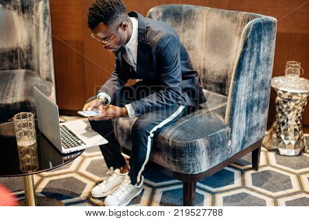 African Employee wearing suit working online on laptop