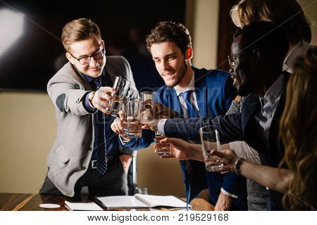 Successful business people are clinking glasses of champagne and smiling while celebrating in meeting