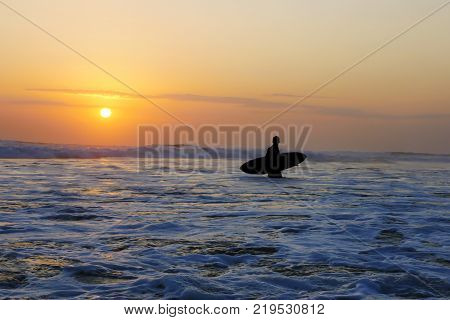Silhouette of unknown anonymous surfer man holding surf board after surfing on sunset with amazing beautiful sunlight with orange sky and silver sea water in Summer sport and holiday vacation concept poster
