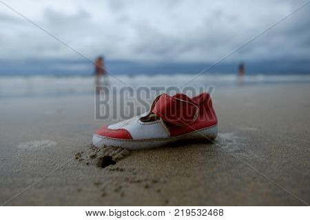 Lost child shoe on stormy sandy beach.