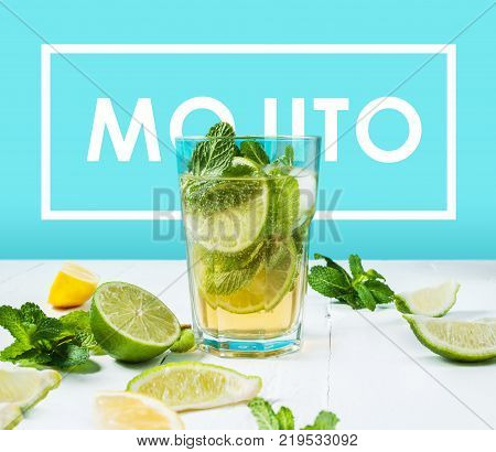 Mojito cocktail with lime and mint in highball glass on a wood table. Blue background.