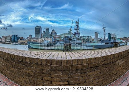 Panoramic in fish-eye view with the historic HMS Belfast battleship and skyscrapers from Canary Wharf on the Bank of River Thames.