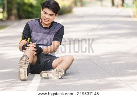 Asian young sport man knee injury from jogging