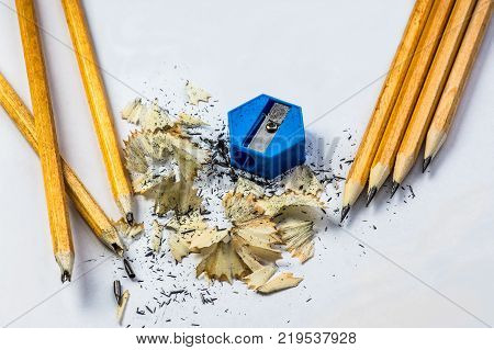 broken and sharpened pencils with sharpener and shavings