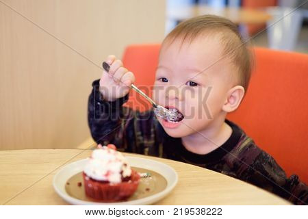 Cute Happy Smiling little Asian 18 months / 1 year old toddler baby boy child eating cupcake with fork he's sitting on chair at restaurant Children & Self feeding concept Soft & Selective focus