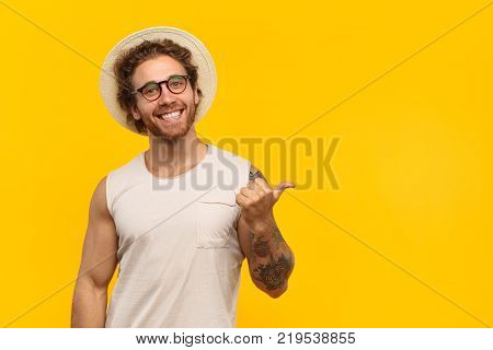 Handsome cheerful man in hat and eyeglasses pointing away while smiling at camera.