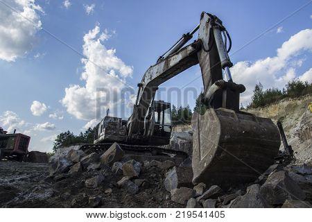 Excavator and basalt columns rocks. Heavy industry. The excavator produces stone from basalt pillars.
