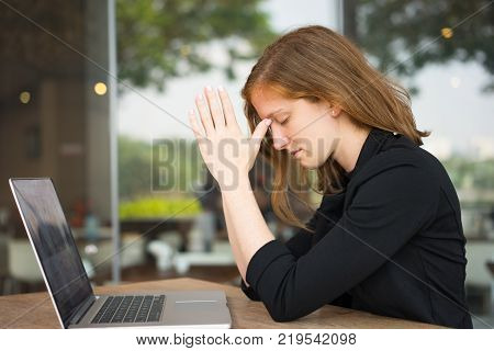 Portrait of young woman with closed eyes sitting at table with laptop and praying. Business woman learned shock news and trying to calm down. Good or bad news concept