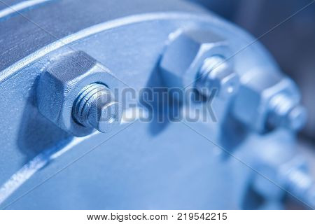 Joint of two flanges by bolts and nuts, selective focus only on first bolt