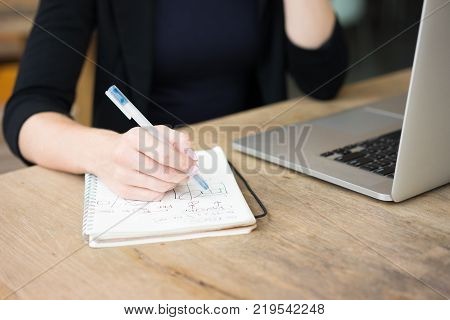 Closeup of woman hand drawing flowcharts in notepad. Student copying flow from laptop screen to notebook. Education or work tools concept