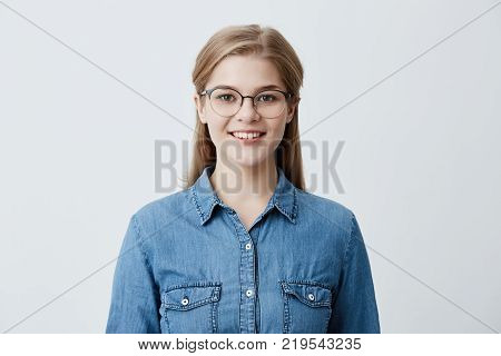 Horizontal portrait of good looking caucasian female with blonde straight hair, wearing glasses and denim shirt, smiles happily, has good mood after successful day at university, glad and pleased to pose at camera