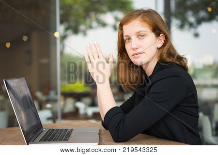 Portrait of young woman at table with laptop and hands in praying gesture. Business woman pondering deal at office outdoor cafe. Business and work balance concept