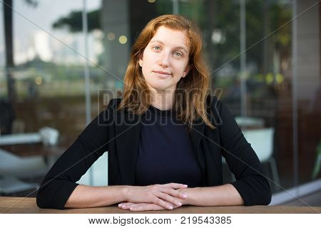 Portrait of reflecting attractive woman sitting at outdoor cafe and grinning at camera. Recent graduate waiting for interview with employer. Business and human resource concept