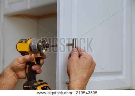Hand on handle installation of door handles on opening cabinet door in kitchen with a screwdriver
