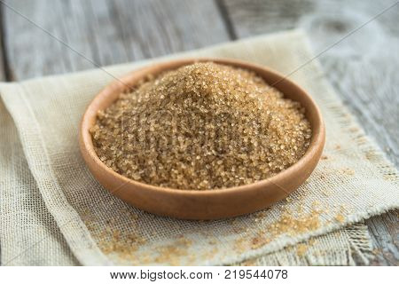 brown sugar in a bowl on a wooden table. Brown sugar . cane sugar