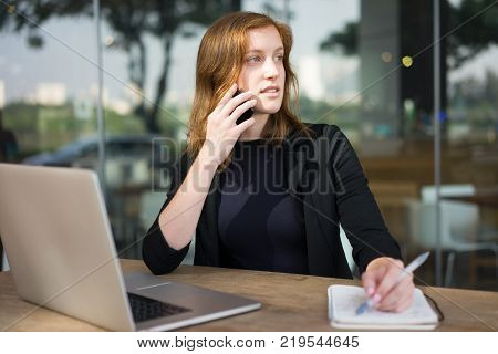 Pensive young woman sitting at outdoor cafe with laptop and speaking on phone. Business lady talking by phone and waiting for partner at office cafe. Business and communication concept