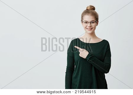 Isolated studio shot of cheerful young female customer or student with blonde hair in casual green sweater and eyeglasses smiling broadly, pointing her index finger at gray copyspace wall for your text or advertising information