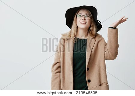 Unhappy young woman frowns face in displeasure, shrugs shoulders, has bad mood, being upset because of rainy weather, checks weather it continues raining. Student girl in coat, eyeglasses and black hat gestures actively indoors.