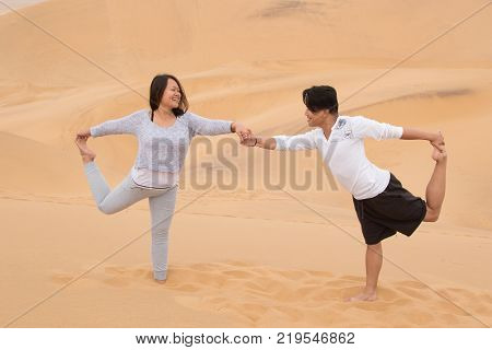 An Indonesian girl and Filipino boy doing yoga exercises on Dune 7, the highest sand dune in the world, in Walvis Bay, Namibia