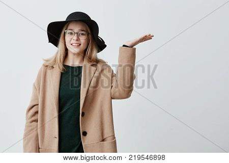 Portrait of young female feeling tired and unhappy, gesturing with open palms, looking up, fed up with stressful bad working day, wants to go out but is afraid of rain. Female student in coat and hat puzzled because of bad weather conditions.