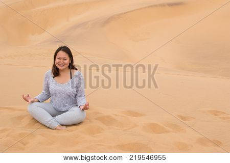 An Indonesian girl doing yoga on Dune 7, the highest sand dune in the world, in Walvis Bay, Namibia