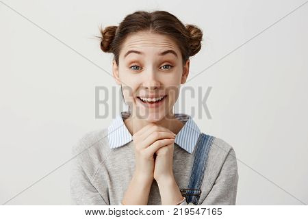 Cute adult girl with odango hairstyle looking on camera with smile holding fists together. Thrilled beautiful woman having shining with happiness after getting marriage proposal. Facial expressions Copy space.