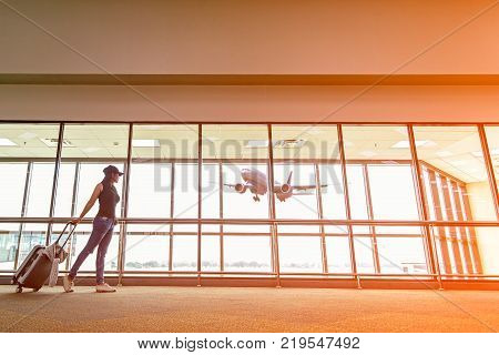 Traveler woman plan and backpack see the airplane at the airport glass window girl tourist hold bag and waiting near luggage in hall airplane departure. Travel Concept .