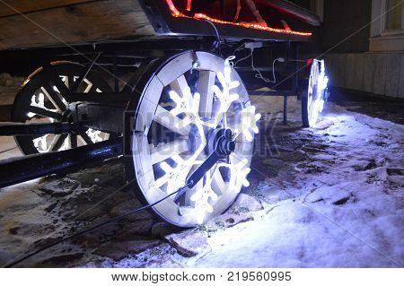 Glowing wheels Christmas garland in the form of snowflakes on wooden cart wheels. Christmas decorations of the wheels.