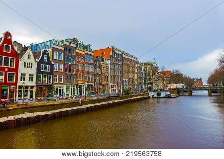 Amsterdam, Netherlands - December 14, 2017: The people going near most famous canals and embankments of Amsterdam city during sunset. General view of the cityscape and traditional Netherlands architecture at Amsterdam, Netherlands on December 14, 2017