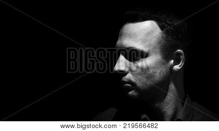 Closeup studio profile portrait of young adult European man isolated over black background low key black and white photo