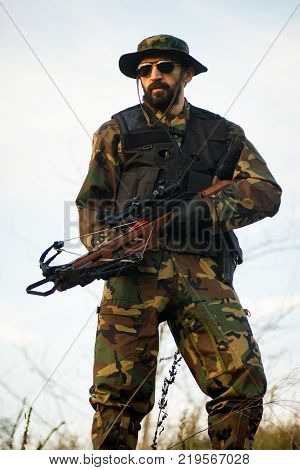 Military man or hunter in military uniform with crossbow weapon is standing outdoors in nature.