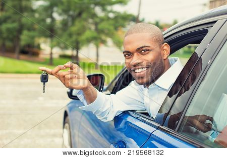 Closeup portrait happy smiling young man buyer sitting in his new blue car showing keys isolated outside dealer dealership lot office. Personal transportation auto purchase concept