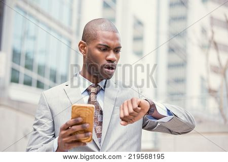 Business and time management concept. Stressed business man looking at wrist watch running late for meeting standing outside corporate office. Worried face expression. Human emotion