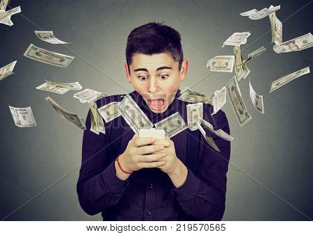 Technology online banking money transfer e-commerce concept. Amazed young man using smartphone with dollar bills flying away from screen isolated on gray wall background.