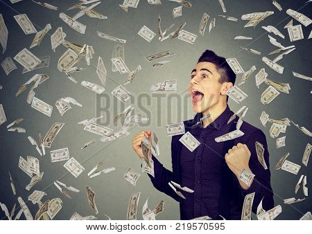 Portrait happy man exults pumping fists ecstatic celebrates success under money rain falling down dollar banknotes isolated on gray wall background