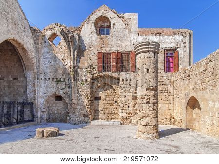 Ancient theaterin Rhodes town on Rhodes island Greece with view of ruins of a pillar
