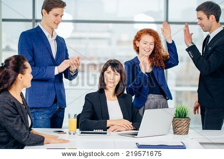 People Working On Project In Office. Beautiful Smiling Female And Handsome Male Co-Workers standing near Table, Looking At Laptop And Sharing Ideas